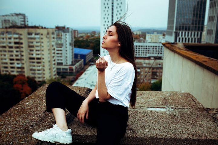 Девушка курит на крыше
