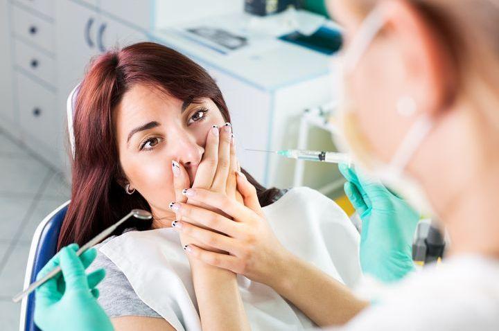 Испуганная девушка в кабинете стоматолога
