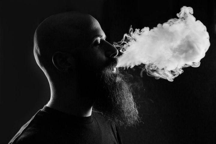 Мужчина с бородой курит