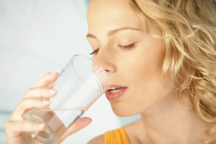 Девушка подносит стакан к губам
