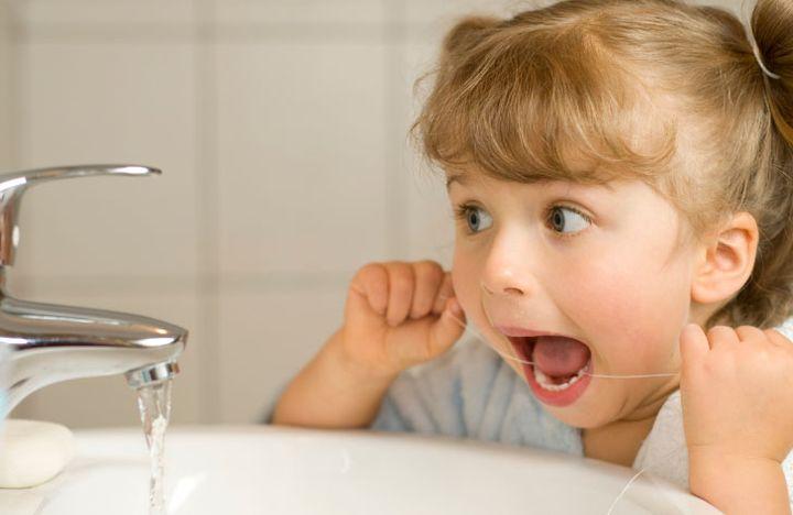 Ребенок чистит зубы нитью